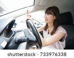 driving woman using smartphone | Shutterstock . vector #733976338