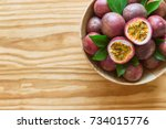 Small photo of Fresh passion fruit in wood bowl on wood table in top view flat lay with copy space for background or wallpaper. Ripe passion fruit so sweet and sour. Tropical fruit.