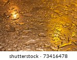 Metallic surface, shining in yellow evening light with raindrops on it - stock photo