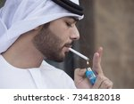 Small photo of Close-up of a Arab young man wearing kandoura and agal, lighting a cigarette.