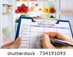 person's hand filling meal plan ... | Shutterstock . vector #734191093