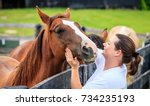 Stock photo young woman is petting a horse on a farm in kentucky 734235193