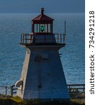 Small photo of The green light shining on the lighthouse on Cape Enrage, New Brunswick, Canada