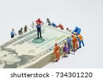 Small photo of Miniature figurine toys holding US twenty dollar notes - slave to money and work concept. Focus on the businessman folding arms in the centre. Ruthless and slave to work concept.