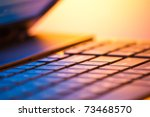 laptop computer detail with copy space and shallow depth of field in warm light - stock photo
