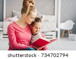 mother teaches her daughter to... | Shutterstock . vector #734702794