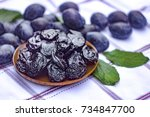 dried prunes in a dish on a... | Shutterstock . vector #734847700