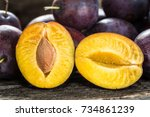 fresh blue plums on wooden table | Shutterstock . vector #734861239
