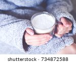 the girl is holding a mug of... | Shutterstock . vector #734872588