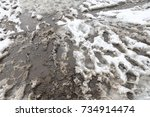 Dirty Road With Foot Prints On...