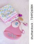 Small photo of pink plastic baby bib ,hairbrush and diapers