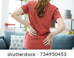 young woman with back pain | Shutterstock . vector #734950453