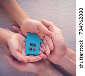 Small photo of Adult and child hands holding paper house, family home, homeless shelter and real estate concept