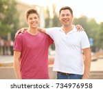 teenager boy with father in park | Shutterstock . vector #734976958