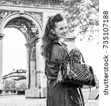 Small photo of Stylish autumn in Paris. Portrait of happy young fashion-monger in trench coat in Paris, France