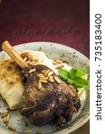 Small photo of Lamb shank with pine nuts on a white plate isolated top view