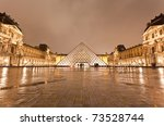 PARIS - DECEMBER 7: The Louvre Museum at the rainy night on December 7, 2010 in Paris France.The Louvre is the biggest Museum in Paris displayed over 60,000 square meters of exhibition space. - stock photo