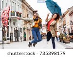 Small photo of Two female best friends making fun at the city street.Raining day and autumn concept.