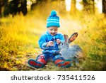 baby boy in autumn forest with... | Shutterstock . vector #735411526