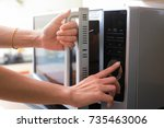 woman's hands closing microwave ... | Shutterstock . vector #735463006