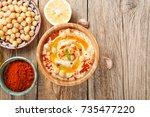bowl of homemade hummus on... | Shutterstock . vector #735477220