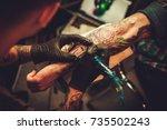 tattoo artist makes a tattoo on ... | Shutterstock . vector #735502243