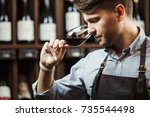Small photo of Sommelier smelling flavor of red wine in bokal on background of shelves with bottles in cellar. Male appreciating color, quality and sediments of drink. Professional degustation expert in winemaking.