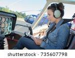 female helicopter pilot reading ... | Shutterstock . vector #735607798