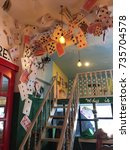 """Small photo of Negros Oriental, Philippines; October 16, 2017: Oversized playing cards and books hang from the ceiling of an """"Alice in Wonderland"""" themed room at the Chapters Cafe in Dumaguete City."""