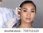 Small photo of Asian Doctor Nurse check face cheek bone structure before plastic surgery and inject beauty chemical syringe to patient with acne, wart, Studio lighting grey background