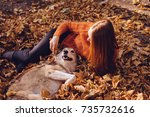 Stock photo red haired girl in a fashionable orange sweater plays with her dog in fallen autumn leaves 735732616