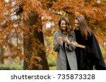two pretty young women using... | Shutterstock . vector #735873328