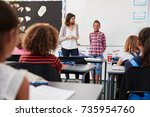 Small photo of Teacher and pupil stand at front of elementary school class