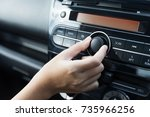 Women turning button on car radio for listening to music - stock photo