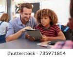 teacher and schoolboy using... | Shutterstock . vector #735971854