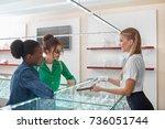 female jeweller helping two... | Shutterstock . vector #736051744