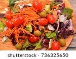 fresh salad on a wooden plate   Shutterstock . vector #736325650