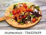 fresh salad on a wooden plate   Shutterstock . vector #736325659
