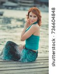 Small photo of Amazing beautiful lady girl woman with red flame hair wearing fancy fashion green clothes posing sitting on wooden pier jetty wth port boats on background Adoring scene of sea mermaid.