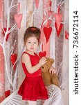 Small photo of Young brunette dolly lady girl stylish dressed in red dress strap shoes smiling posing sitting in studio on white chair with teddy bear and tree with hearts with pout lips and pink cheeks