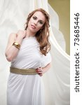 Small photo of a studio portrait of a beautiful young woman, wearing a long, white, ancient greek inspired dress, surrounded by a flowy, wavy white fabric.