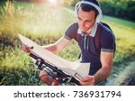Small photo of Young adventurer with bicycle searching the map during his journey. Sport, lifestyle, adventure