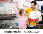 Stock photo portrait cheerful father and daughter choosing pretty bird for keeping in pet shop 737053660