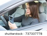 Happy teen girl driving a new car while texting