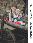 Small photo of Sisters two with blue eyes wearing stylish village clothes posing on wooden old style retro wagon cart trundle with apples and red comforter plaid wrap happy together family.