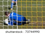 Football player catching the ball in a goal net with grass background - stock photo