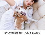 Stock photo girl with gray eyes and charming smile lies on soft sofa and making selfie with her pet indoor 737516398