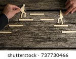 Small photo of Two paper cutout men striving for the same goal climbing steps in opposite directions towards the same platform.