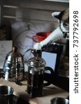 Small photo of The process of brewing coffee in the french press. Cute cat presses the plunger by paw