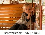 Little Boy Sitting On Bench